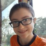 Jojo smiles for the camera, wearing glasses and an orange shirt